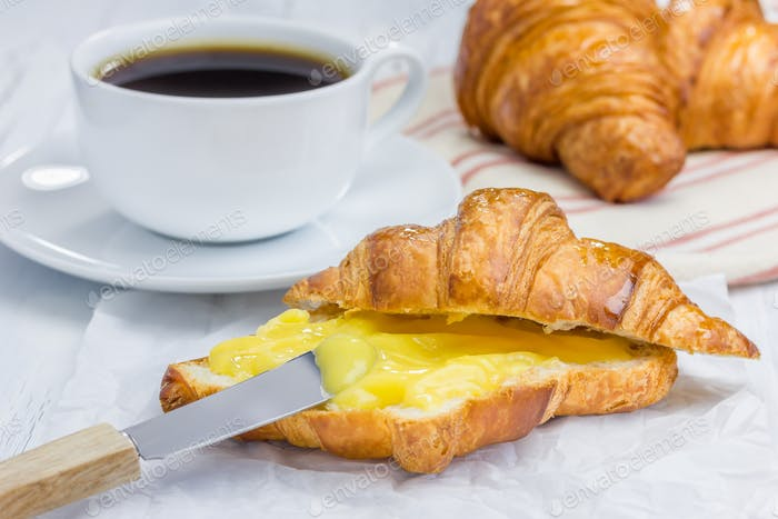 Fresh croissant with lemon curd and cup of coffee
