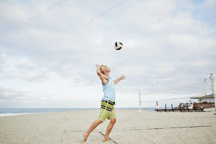 Homme mature debout sur une plage, jouant au beach volley.
