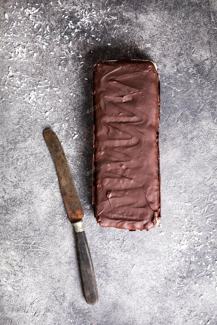 Roher hausgemachter Schokolade Kokosnuss Dessert. Gesundes veganes Lebensmittelkonzept.