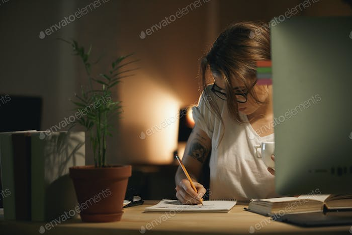 Concentrated young woman designer writing notes using computer