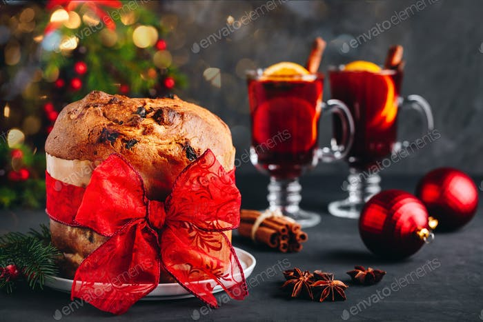 Traditional Christmas Panettone cake with dried fruits decorated with a red ribbon