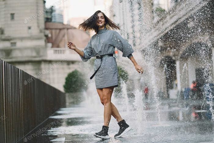 girl playing and dancing around on a wet street