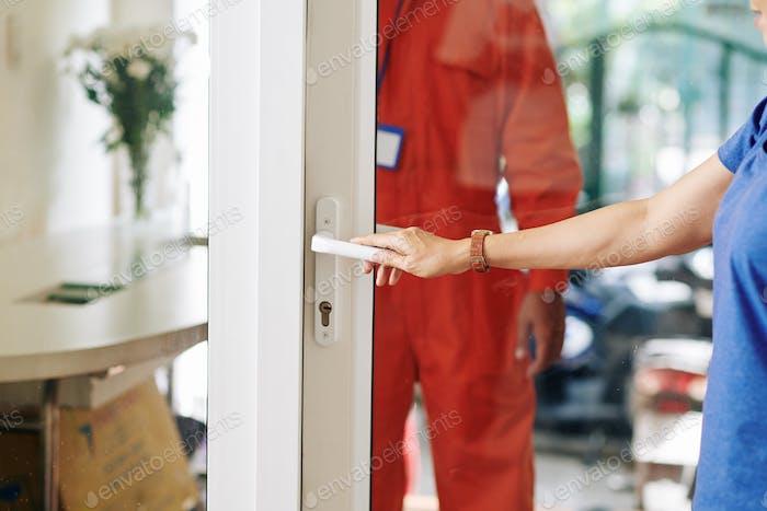 Opening Door To Delivery Man