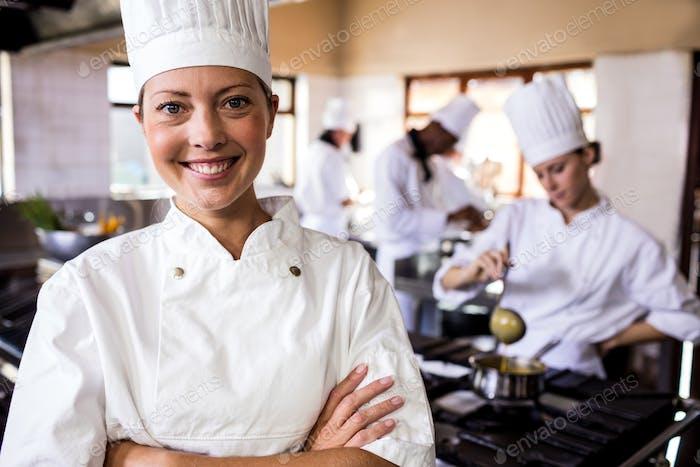 Thumbnail for Chef femenino de pie con los brazos cruzados en la cocina