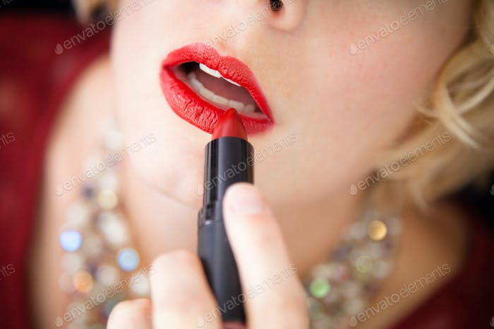 Lady putting lipstick - closeup