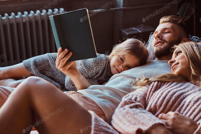 Mama, Papa und Tochter lesen Geschichten zusammen, während sie auf dem Bett liegen.