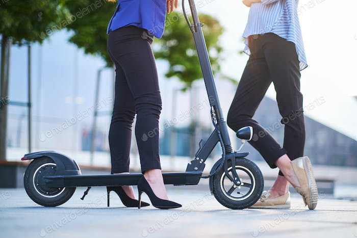 Legs of two females with electrical scooter