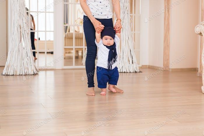 Mama lehrt ihr Sohn erste Baby Schritte drinnen