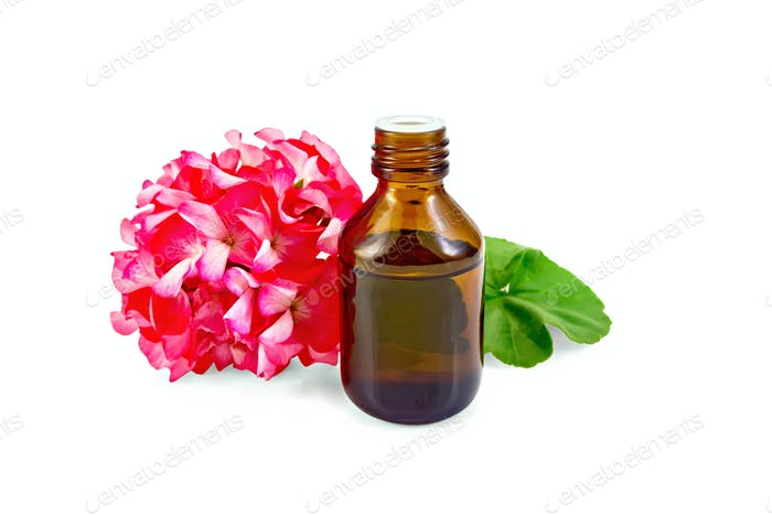 Oil with pink geraniums in dark bottle