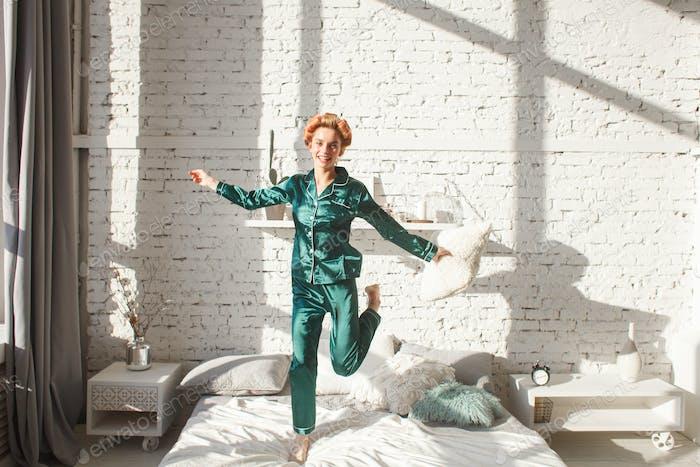 cheerful girl in nightwear jumping on bed