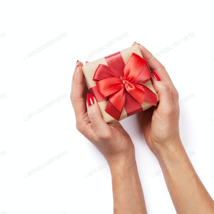 Hands holding christmas or valentines day gift