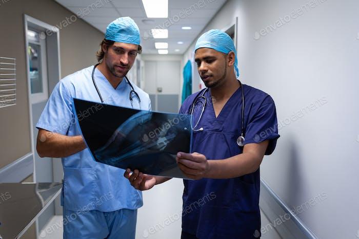 Vorderansicht multiethnischer männlicher Chirurgen diskutieren über Röntgenbericht im Krankenhauskorridor