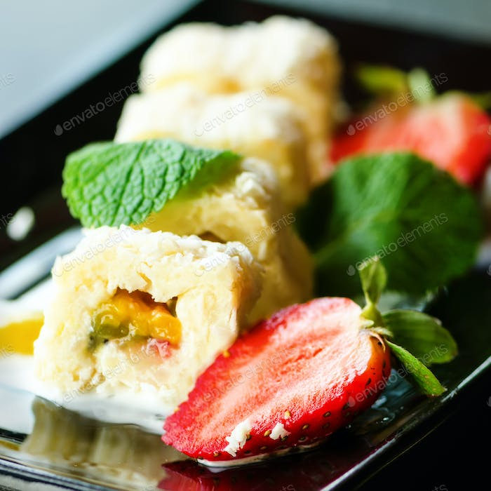 White sweet roll with kiwi, peaches, strawberries, mint. Serverd with almond peach and chocolate