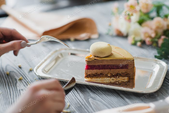 Hands going to eat dessert, yellow mousse cake with almond dacquoise, raspberry confit, crispy layer