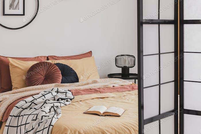 Offenes Buch auf gelber Bettdecke in kleinen gemütlichen Schlafzimmer-Interieur mit Ingwer-Akzenten
