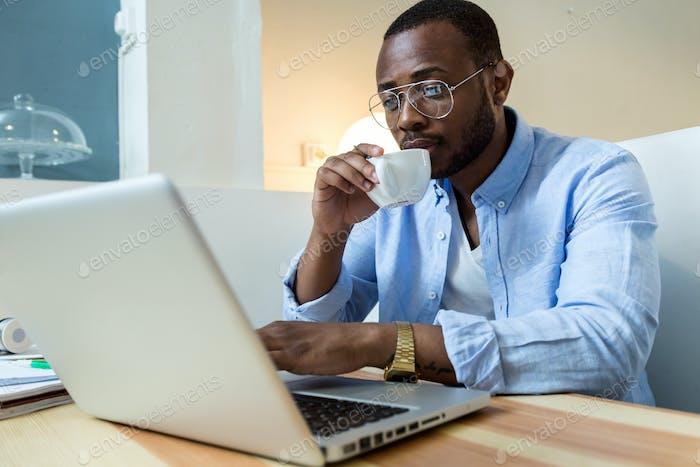 Hübscher junger schwarzer Mann, der mit Laptop zu Hause arbeitet.
