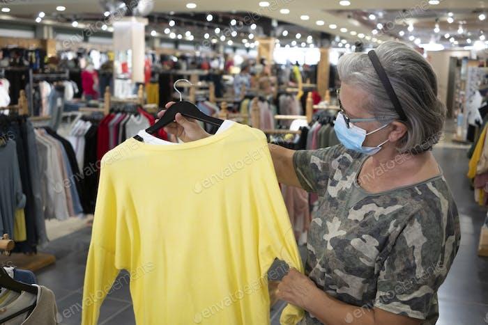 Seniorin mit Gesichtsmaske sucht beim Einkaufen ein gelbes Hemd im Kaufhaus