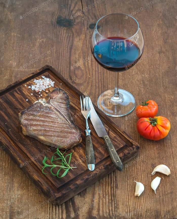 Cooked meat t-bone steak on serving board with garlic cloves, tomatoes, rosemary, spices