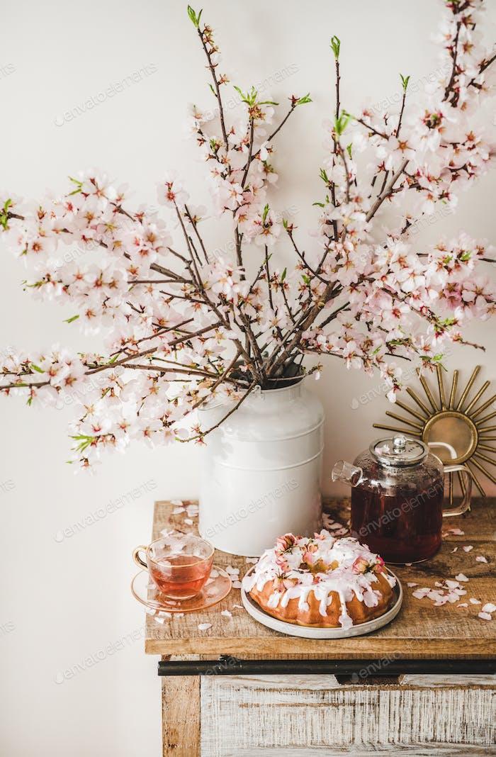 Glutenfreier Bündelkuchen und Tee unter blühenden Ästen