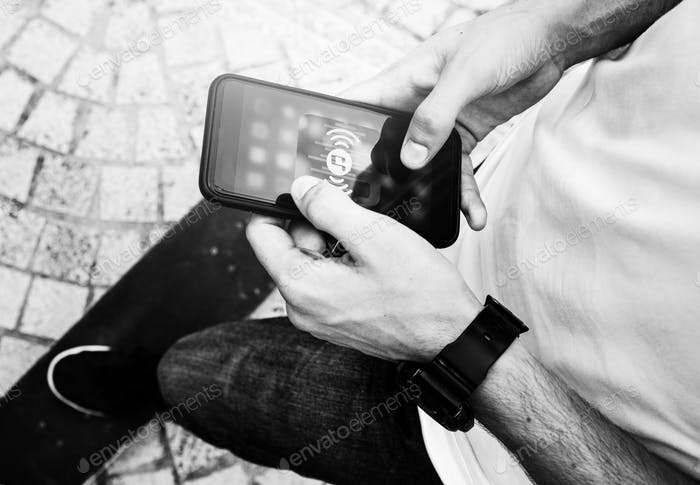 Young adult man using a smartphone music application outdoors