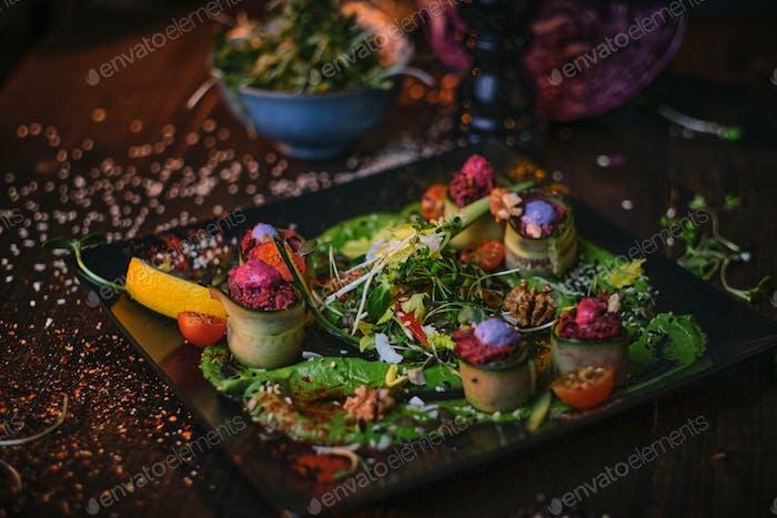 Haute Cuisine vegetarische Teller mit Vorspeisen-Brötchen und eine Schüssel mit Kräutern serviert auf einem Holztisch