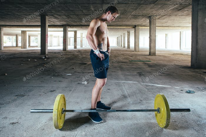 Man standing near barbell in abandoned building