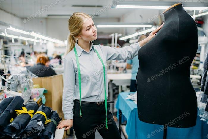 Kleidung Designer misst ein Kleid auf Schaufensterpuppe