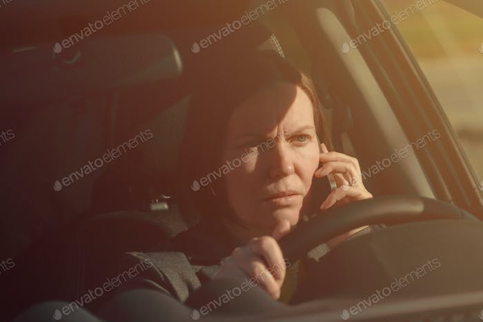 Businesswoman talking on mobile phone in the car