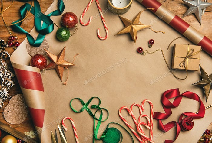 Christmas decorations, balls over wrapping paper, top view