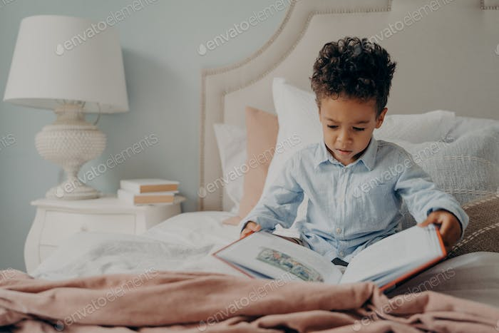 Cute afro american small boy trying to read children's book