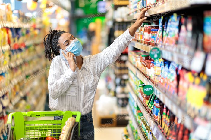 Black Lady Talking On Phone Buying Food In Supermarket Store