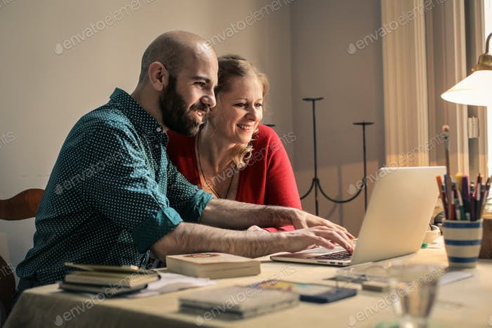 A man and a woman in front of a laptop