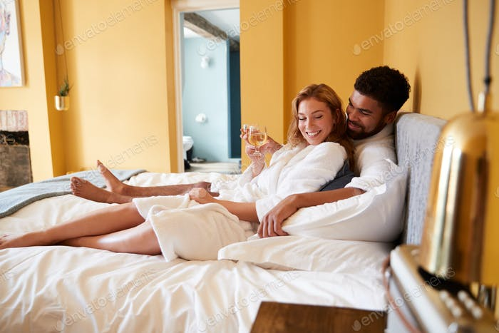 Young mixed race couple relaxing with drinks on a hotel bed