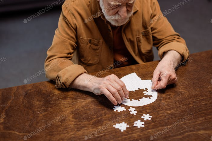 high angle view of senior man playing jigsaw puzzle as dementia therapy