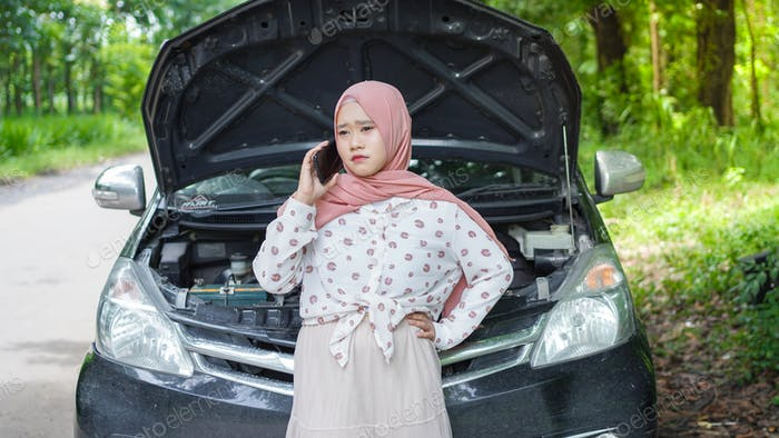 asian women wearing hijab have a trouble with her car