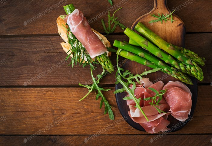 Parma ham, asparagus and arugula on a wooden background. Top view