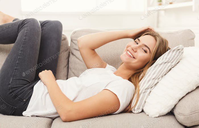 Happy young girl lying on sofa at home