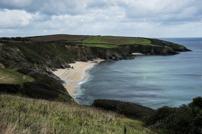 Coastline with cliffs and sandy beach under a cloudy sky.
