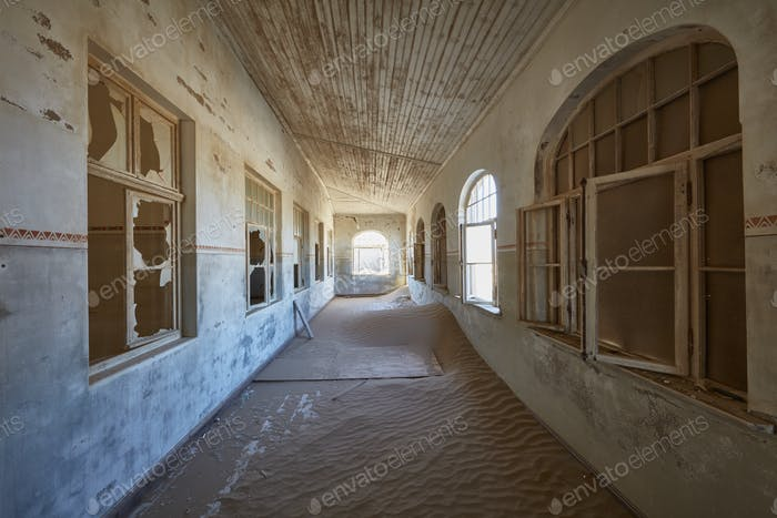 A view of a corridor in a derelict building full of sand.