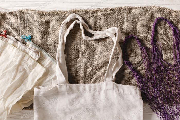 Eco natural cotton reusable bag for shopping flat lay on rustic background