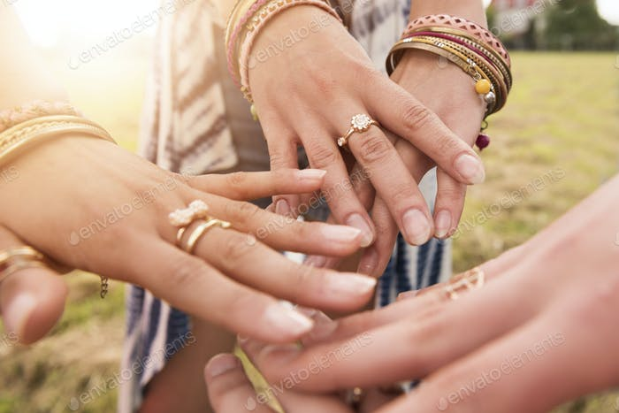 Hands decorated with colorful jewelery