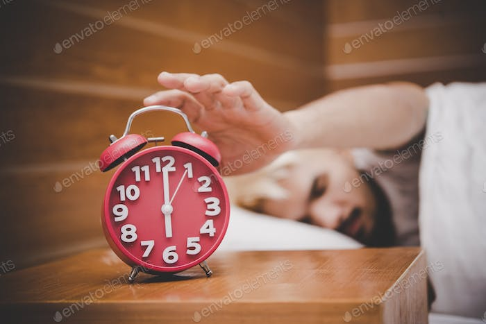Man trying to turn off the alarm clock waking up at morning.