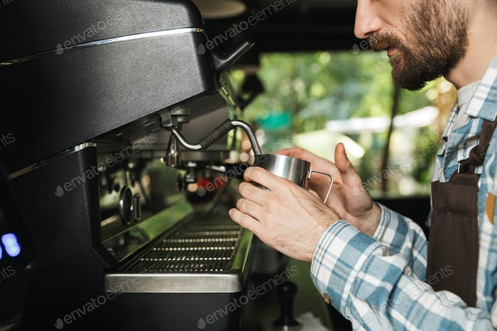 Image of concentrated barista man making coffee while working in