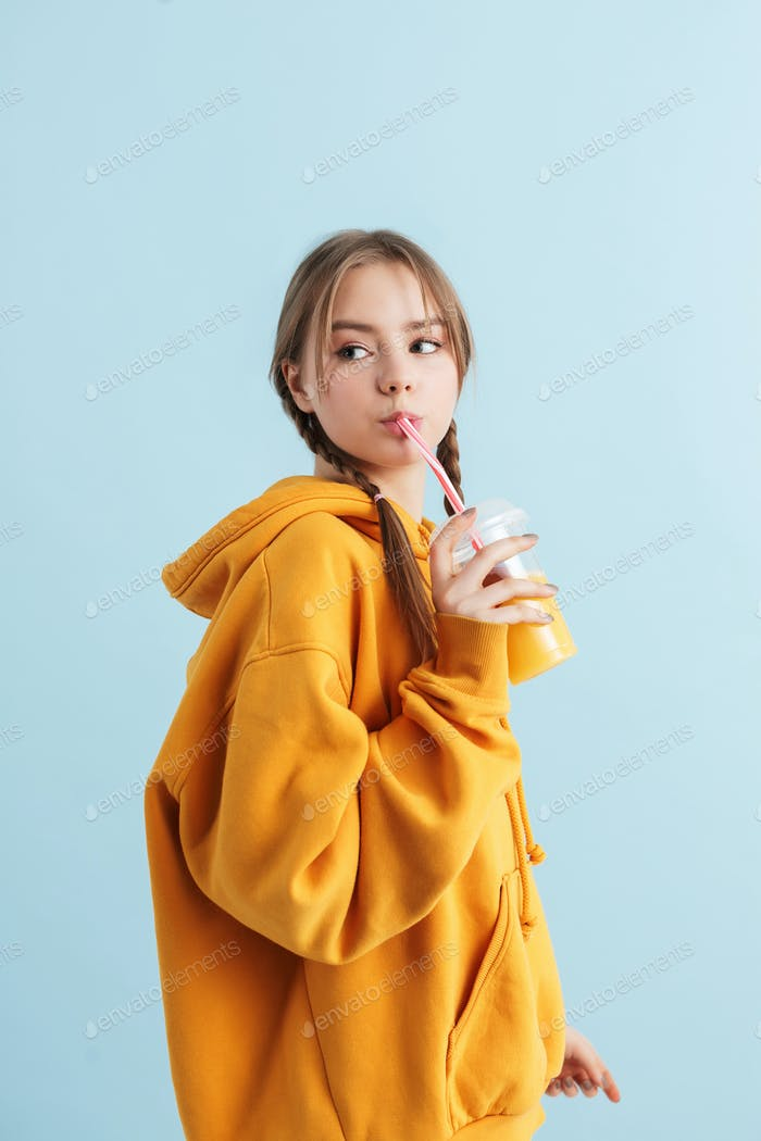 Beautiful teenager girl in hoodie holding plastic cup with orange juice dreamily looking aside