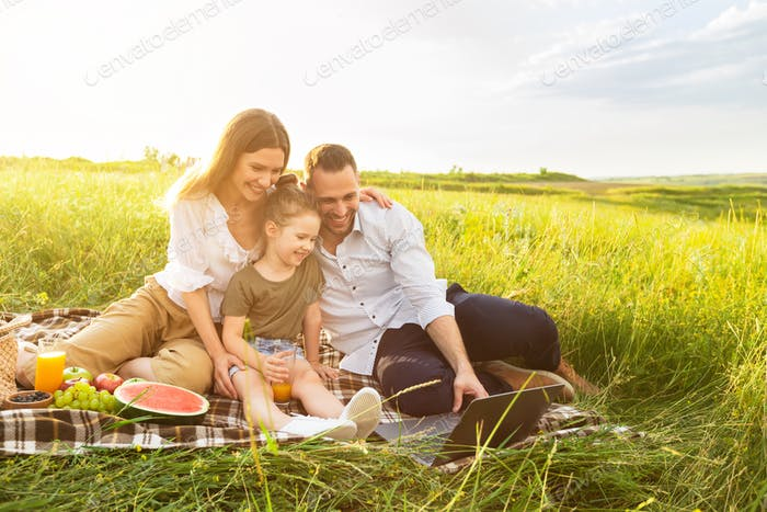 Happy family together on a picnic with laptop