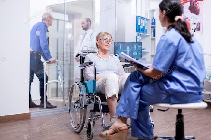 Gelähmte ältere Frau sitzt im Rollstuhl