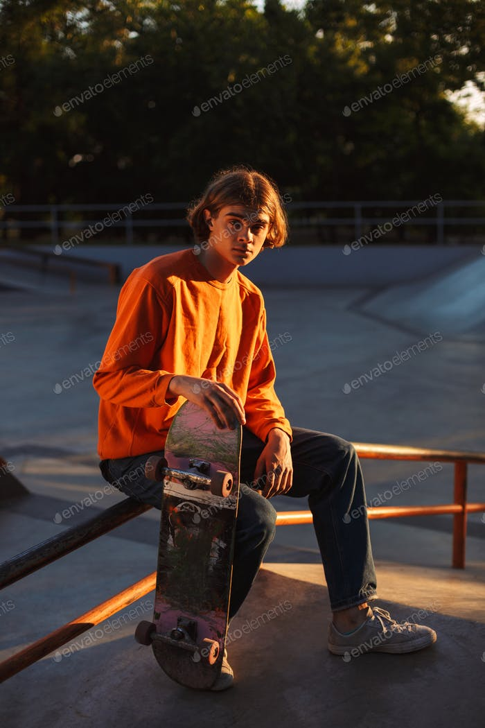 Young skater in orange pullover thoughtfully looking in camera w