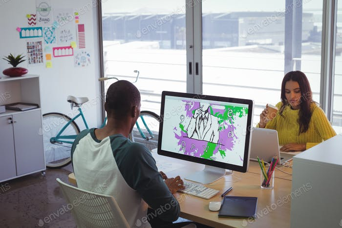 Graphic designers using computer and laptop in creative office