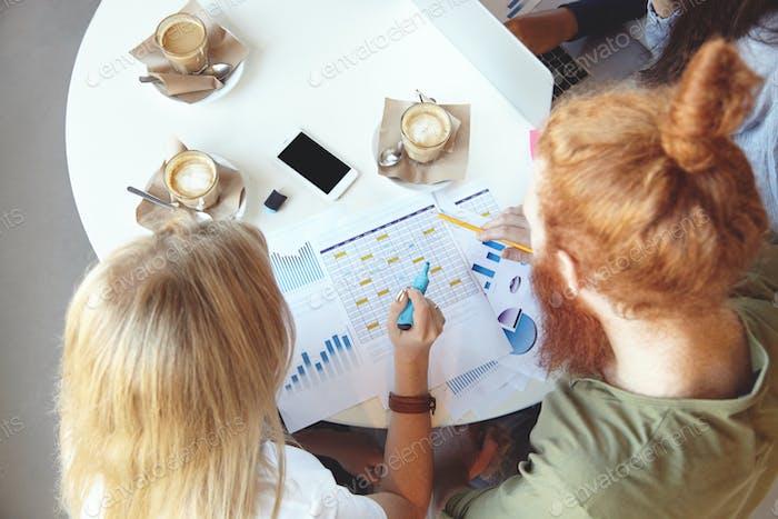 Draufsicht auf junge ehrgeizige und kreative Menschen, Brainstorming, diskutieren Pläne und machen sich Notizen