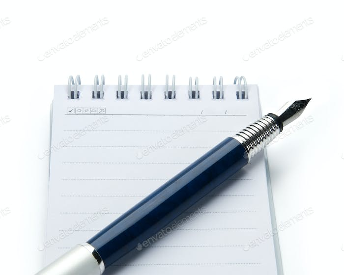 Pen on notebook, isolated on white background.